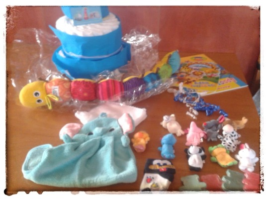 """το """"περιεχόμενο"""" της τούρτας: μια κάμπια- μέτρο για το μωρό, πετσετούλα- ελεφαντάκι, δακτυλοκουκλάκια, καλτσάκια, σαπουνάκια και πολλές πανούλες! όλα υπέροχα και τόσο χρήσιμα!"""